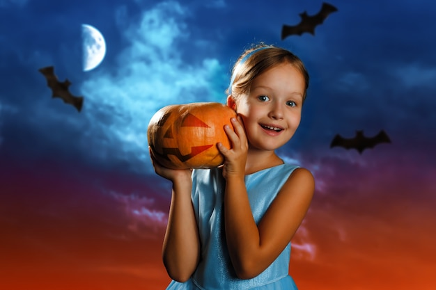 Little girl is holding a pumpkin against the background of the evening moon sky. Premium Photo