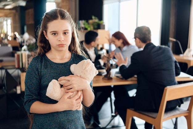 Little girl is hugging teddy bear at office of family lawyer. Premium Photo