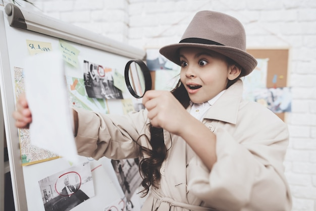Little girl is looking at photos near clues board. Premium Photo