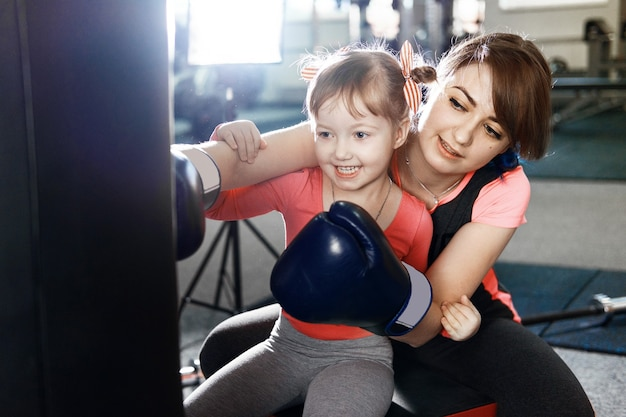 Little girl is practicing boxing, girl teaches mom to box, funny mother and daughter in the gym, happy mother and daughter in the gym Premium Photo