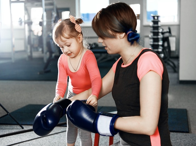 Little girl is practicing boxing, little girl puts on boxing gloves to her mom, mom and daughter getting ready for battle Premium Photo
