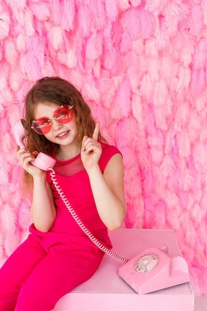 Маленькая девочка сидит в стильных розовых очках на розовом, держит розовый телефон и держит палец вверх Premium Фотографии