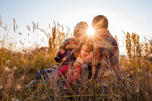 A little girl is sleeping in the arms of her parents Premium Photo