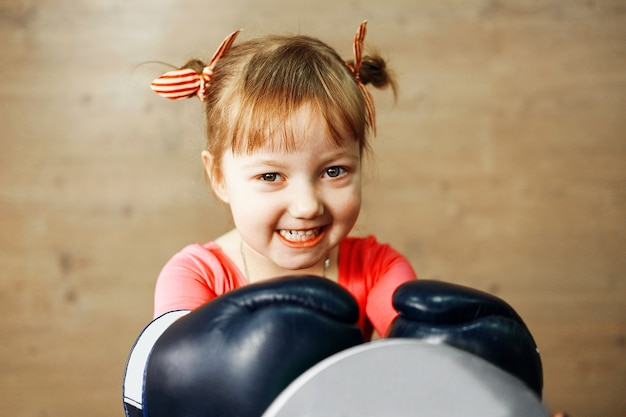 Little girl is training boxing, happy little girl in the gym Premium Photo