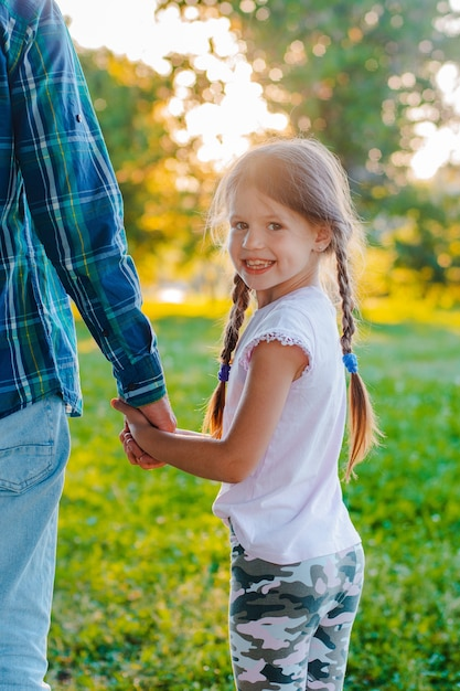 Little girl kid daughter holding her father's hand in the park Premium Photo