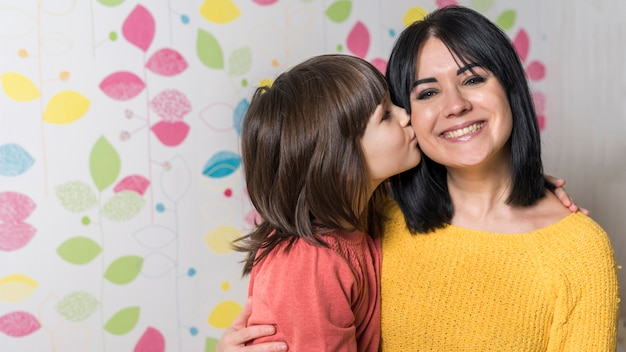 Little girl kissing mother on cheek Free Photo