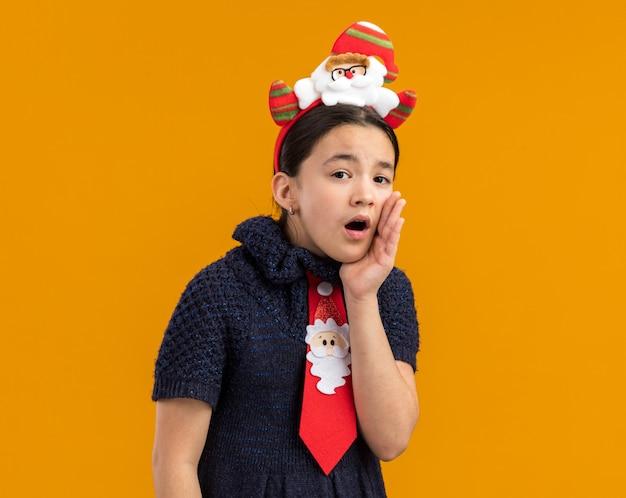 Bambina in abito in maglia che indossa cravatta rossa con bordo divertente natale sulla testa che bisbiglia con la mano vicino alla bocca Foto Gratuite