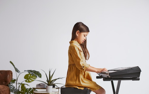 Little girl learning how to play the electronic keyboard Free Photo