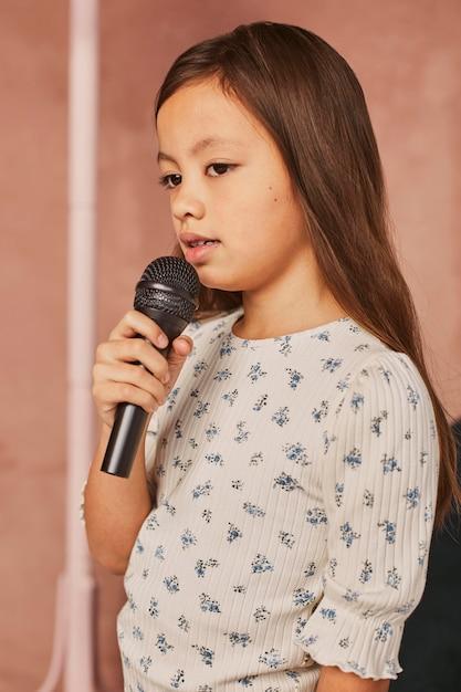 マイクを使って家で歌う方法を学ぶ少女 無料写真