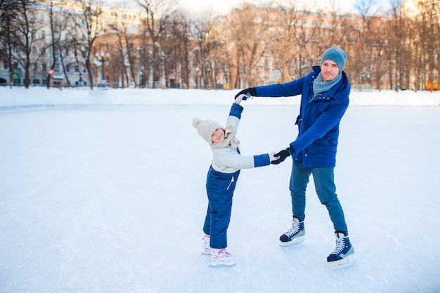 Little girl learning to skate with her father on ice-rink outdoors Premium Photo