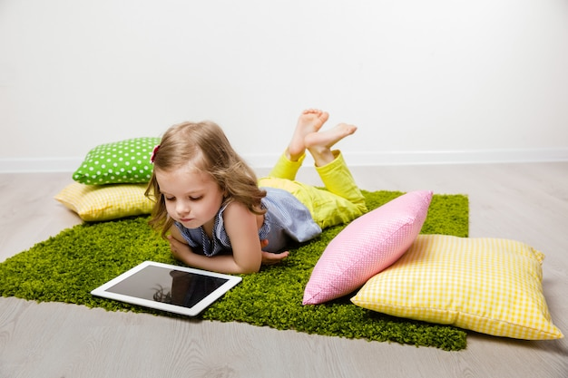 The little girl lies on a rug, watches the tablet. Premium Photo