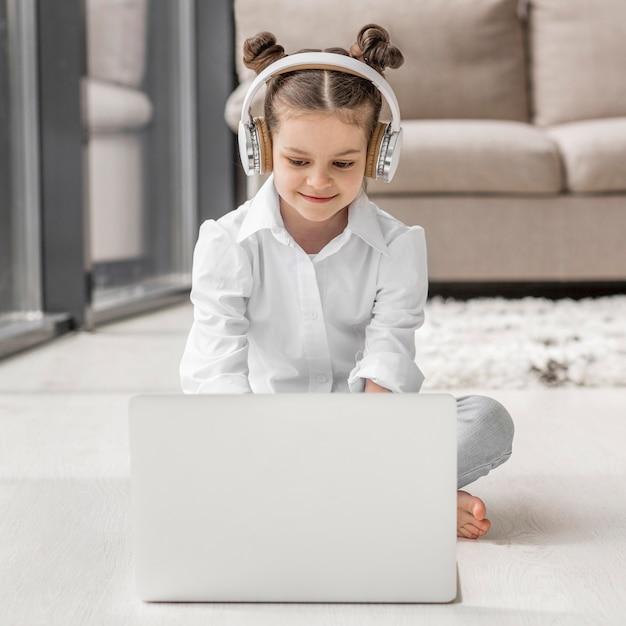 Bambina che ascolta il suo insegnante tramite le cuffie a casa Foto Gratuite