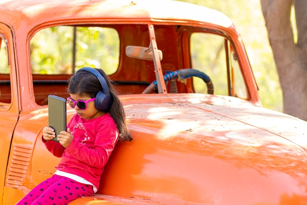 Little girl listening to music on the tablet with her headphones in a truck car Premium Photo