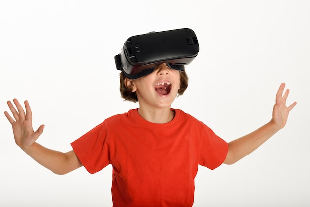 Little girl looking in VR glasses and gesturing with his hands. Free Photo