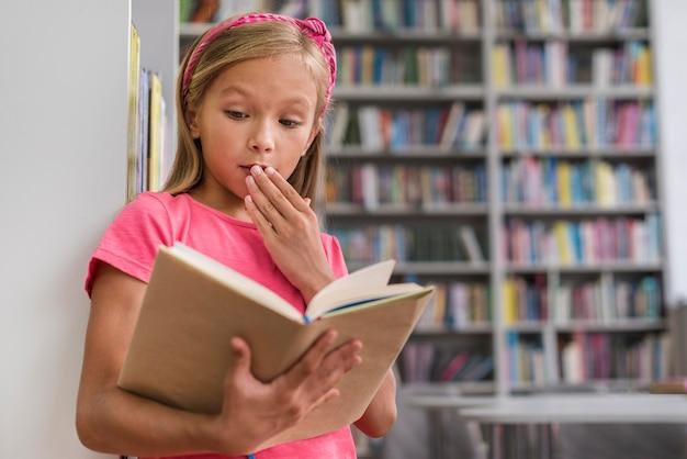 Маленькая девочка выглядит потрясенной, прочитав что-то интригующее Бесплатные Фотографии