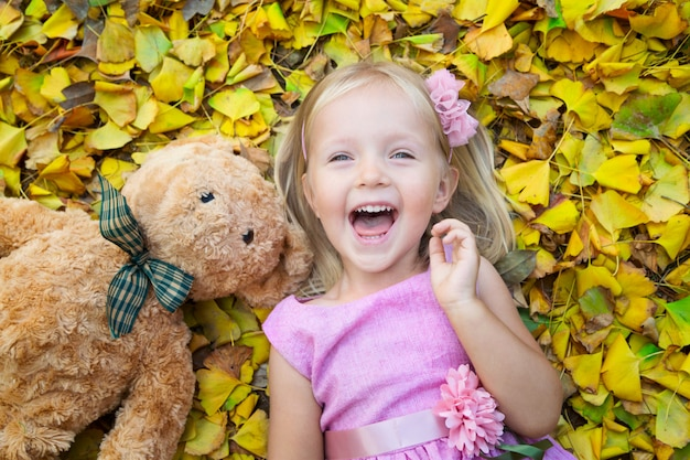 Little girl lying on the street on the fallen leaves with her friend a teddy bear Premium Photo