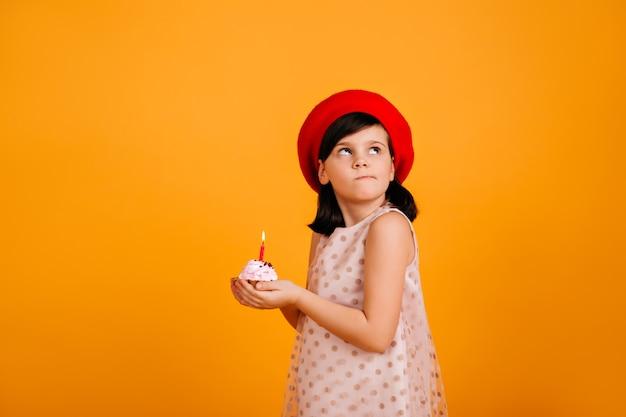誕生日の願い事をする少女。黄色の壁にキャンドルとケーキを保持しているブルネットの子供。 無料写真