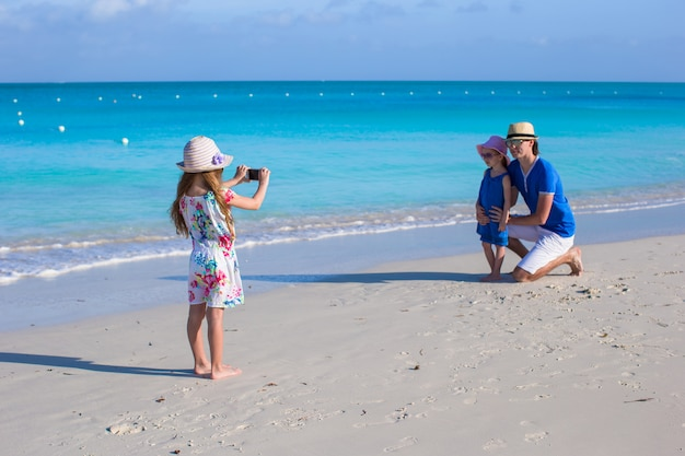 Little girl making photo on phone of her family at the beach Premium Photo