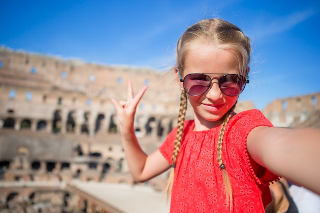 Little girl making selfie in coliseum, rome, italy. kid portrait at famous places in europe Premium Photo