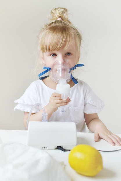 Little girl in a mask for inhalations, making inhalation with nebulizer at home inhaler on the table, indoor, sick child Premium Photo