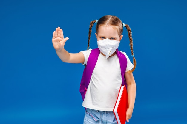 Little girl in a medical mask makes a stop gesture Premium Photo