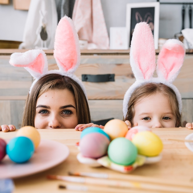 Little girl and mother in bunny ears hiding behind table Free Photo