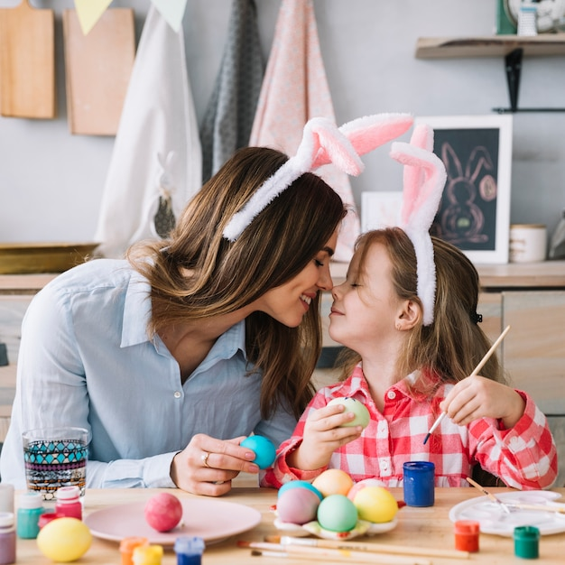 Little girl and mother touching noses while painting eggs for easter Free Photo