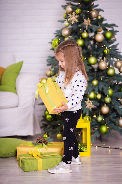 Little girl near the christmas tree opens christmas presents Premium Photo