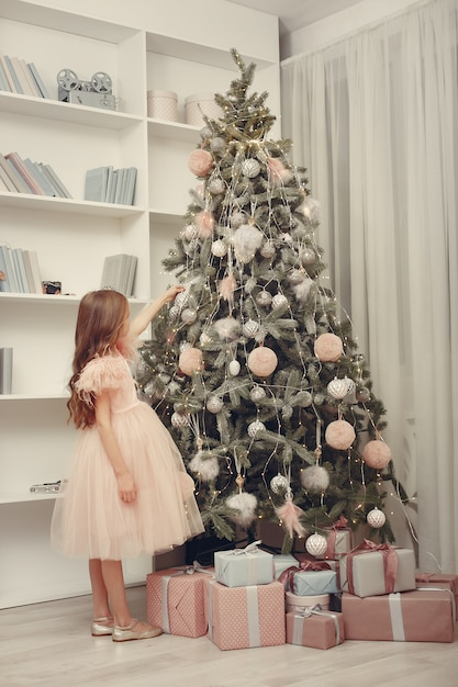 Little girl near christmas tree in a pink dress Free Photo
