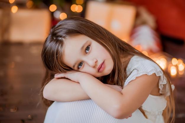 Little girl near the christmas tree smiling Premium Photo