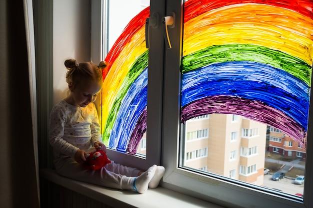 Маленькая девочка на стене картины радуги на окне. детский досуг дома. положительная визуальная поддержка во время карантинного пандемического коронавируса covid-19 в домашних условиях. Premium Фотографии