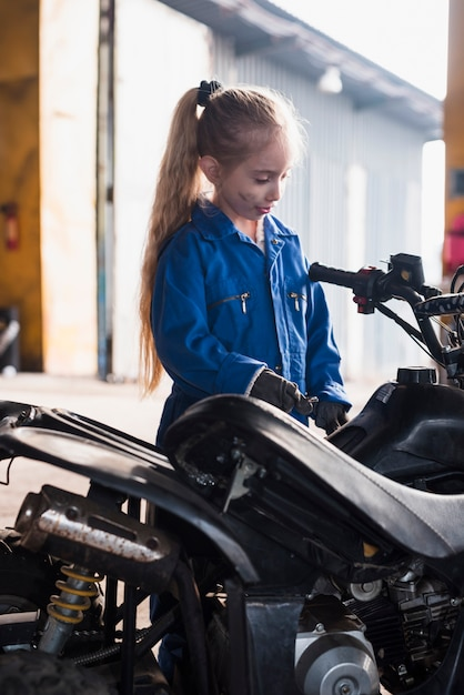 Little girl in overall inspecting quad bike Free Photo
