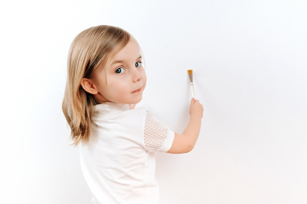 Маленькая девочка, кисть на белой стене Premium Фотографии