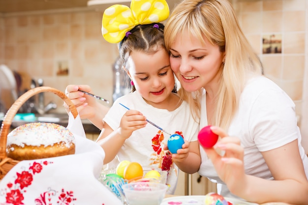 Little girl painting easter eggs with mother Premium Photo