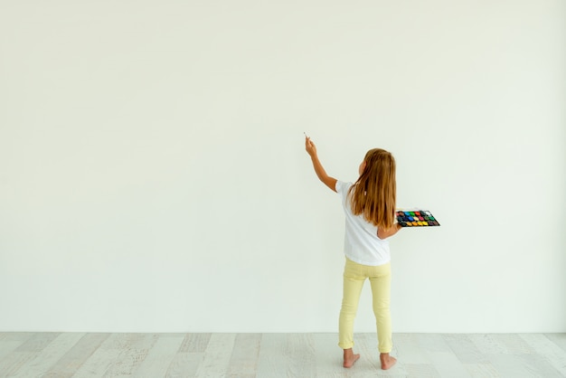 Маленькая девочка, роспись на белой стене в помещении Premium Фотографии