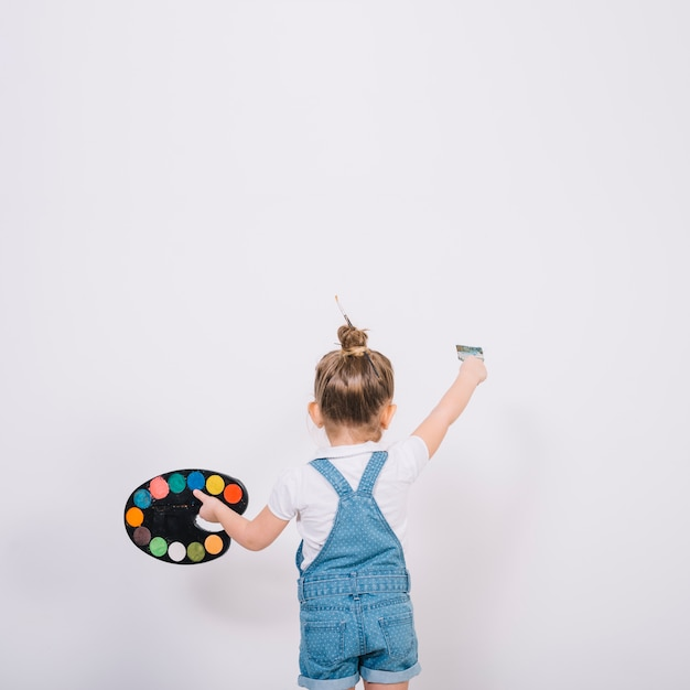 Little girl painting white wall with brush Free Photo