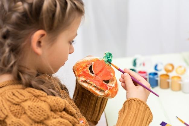Маленькая девочка рисует тыкву цветами. Premium Фотографии