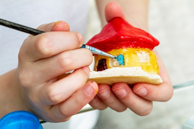 Little girl paints the house from clay or salty dough with acrylic paints. education concept. Premium Photo