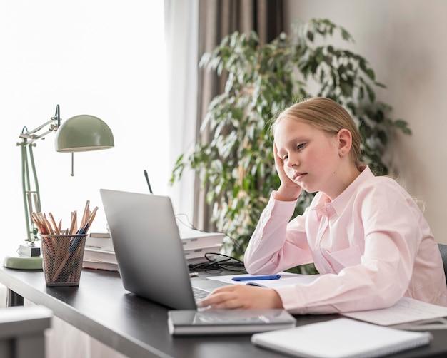 屋内でのオンラインクラスに参加している小さな女の子 無料写真