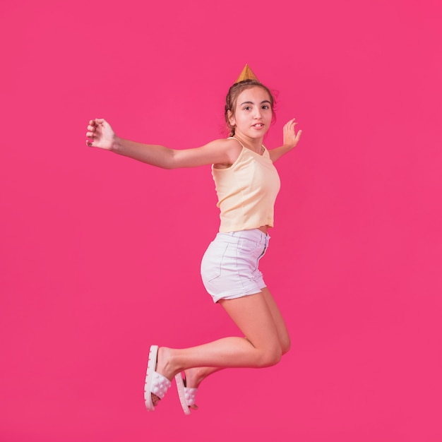 Little girl in party hat jumping on pink backdrop Free Photo