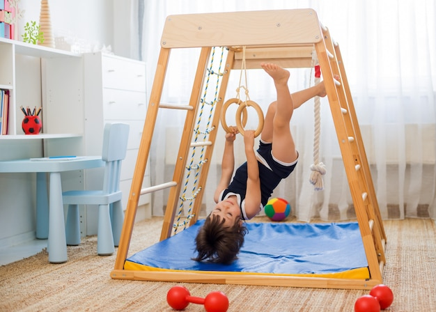 Little girl performs gymnastic exercises on a wooden home sports complex Premium Photo