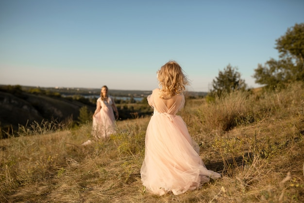A little girl in a pink princess dress goes to meet her mom Premium Photo