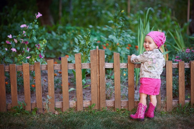 Little girl in pink shoes near the fence Premium Photo