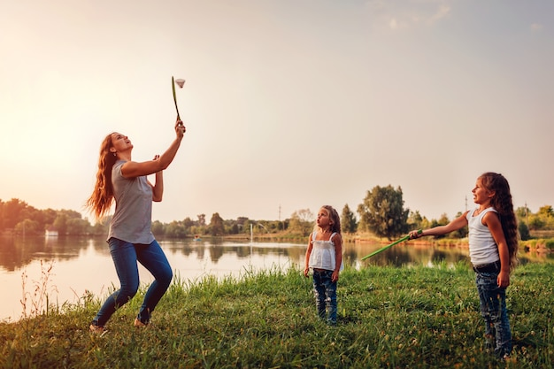 Little girl playing badminton with sister in summer park. Premium Photo