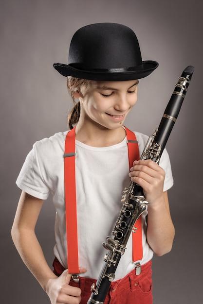 Маленькая девочка играет кларнет на сером Premium Фотографии