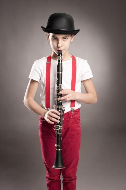 Маленькая девочка играет на кларнете Premium Фотографии