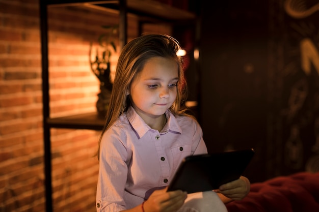 Little girl playing on her tablet Free Photo