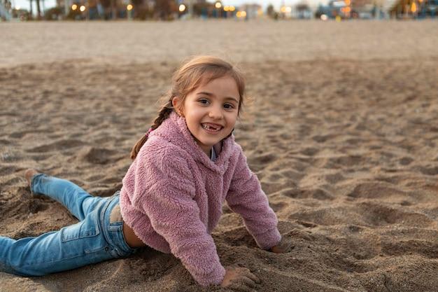 모래에서 노는 어린 소녀 프리미엄 사진