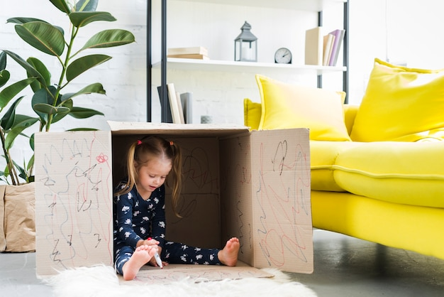 Little girl playing inside cardboard box Free Photo