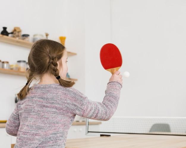 Маленькая девочка играет в настольный теннис в помещении Бесплатные Фотографии